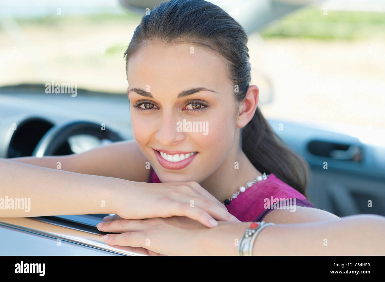 Young woman leaning on car window - Stock Image