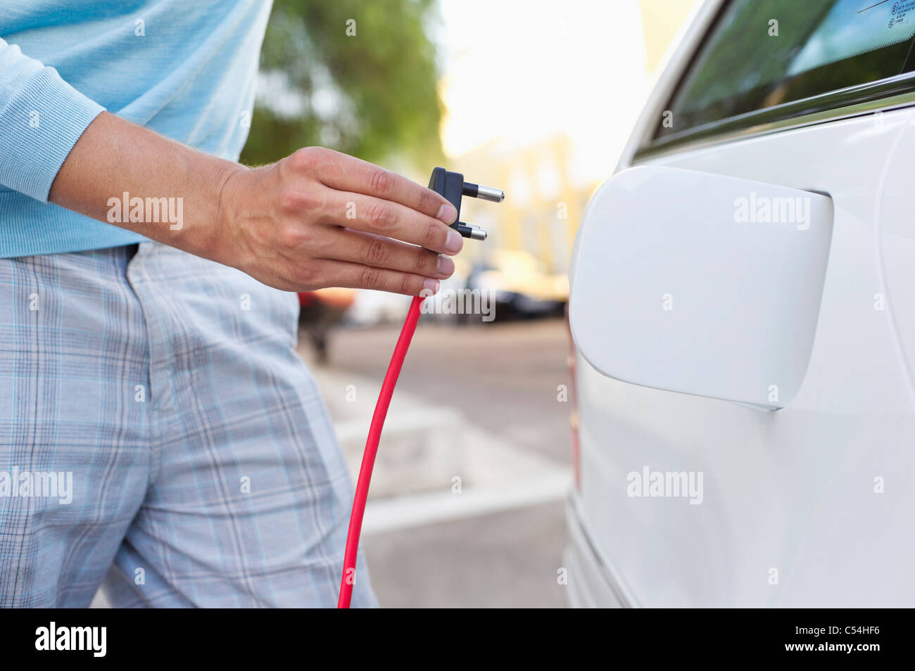 Mid section view of a mid adult man charging the electric car - Stock Image