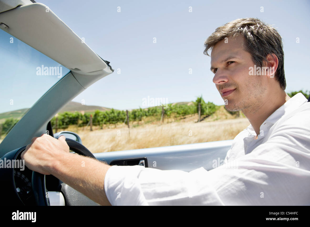 Mid adult man driving a convertible car - Stock Image