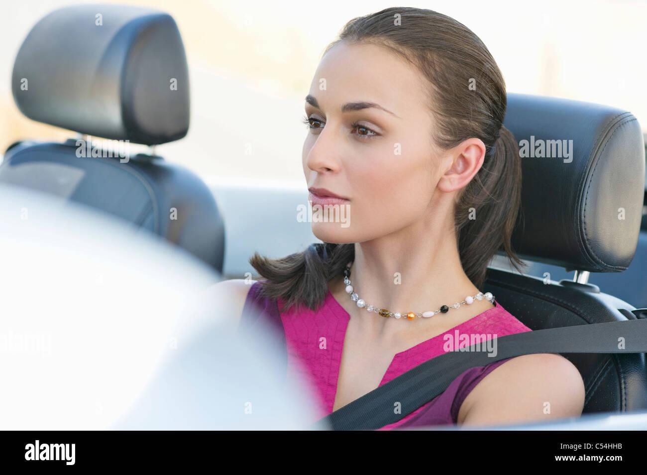 Young woman driving a convertible car - Stock Image