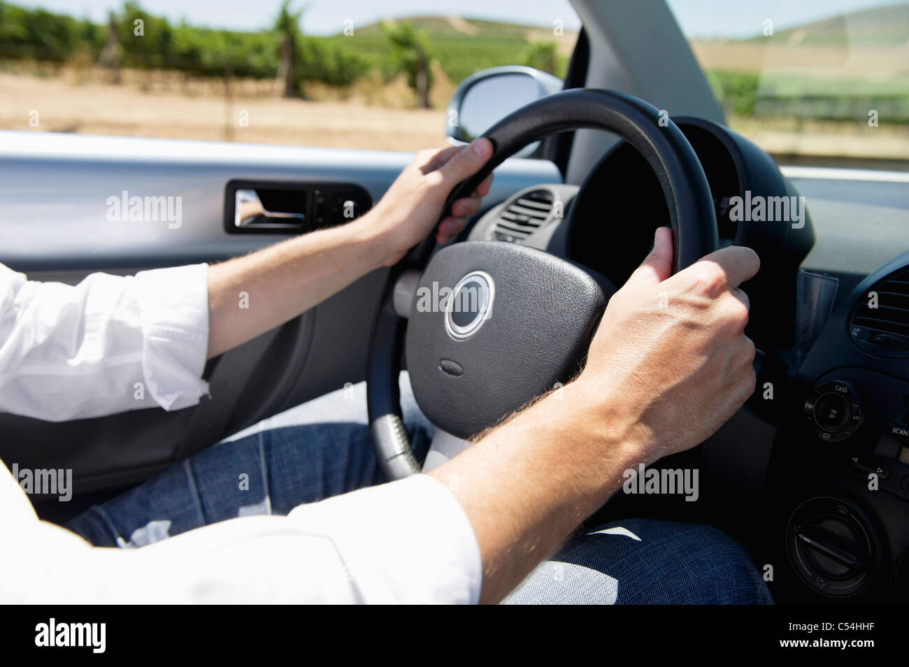 Mid adult man's hand holding a steering wheel of convertible car - Stock Image