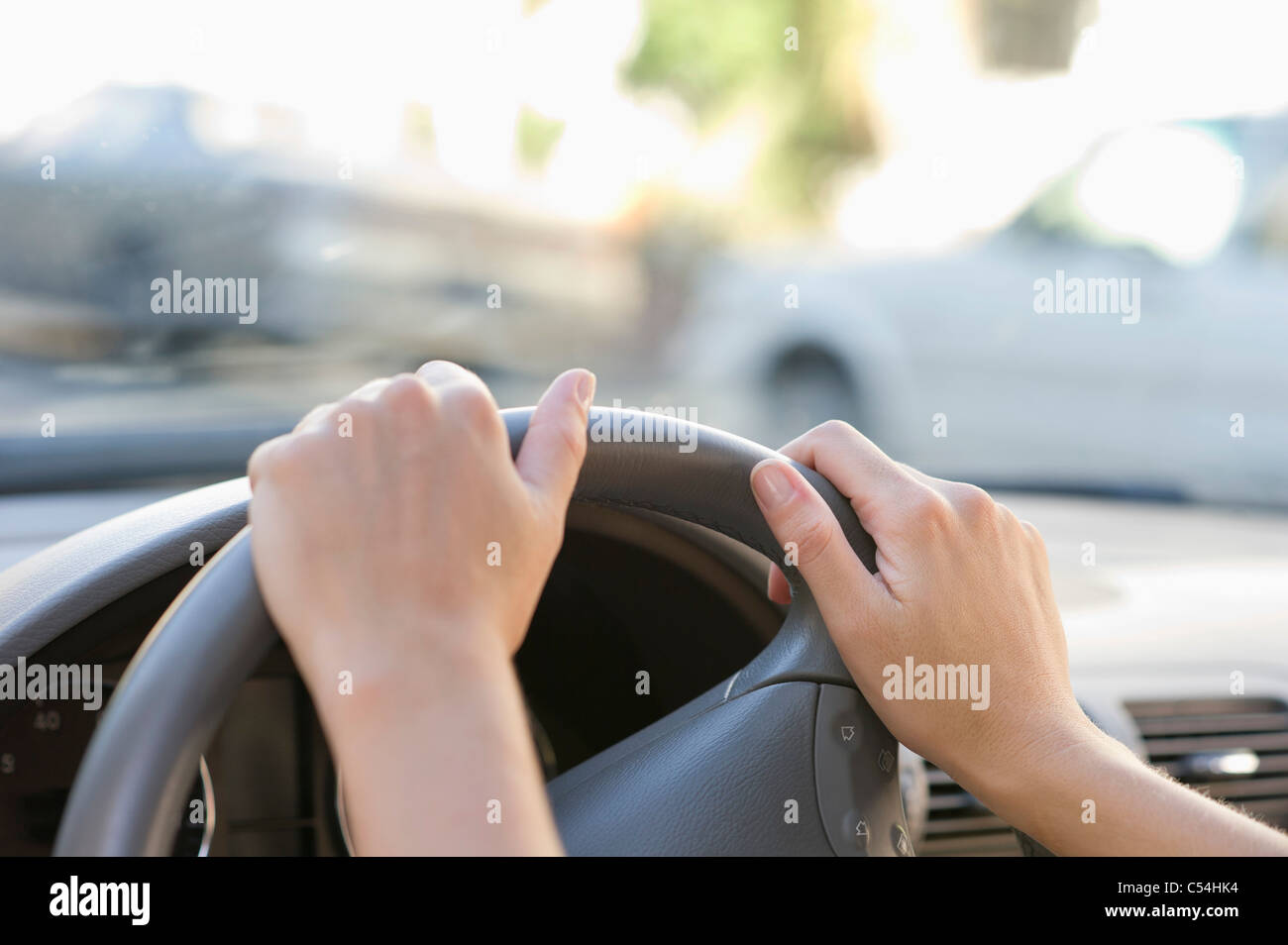 Close-up of human hand holding steering wheel - Stock Image