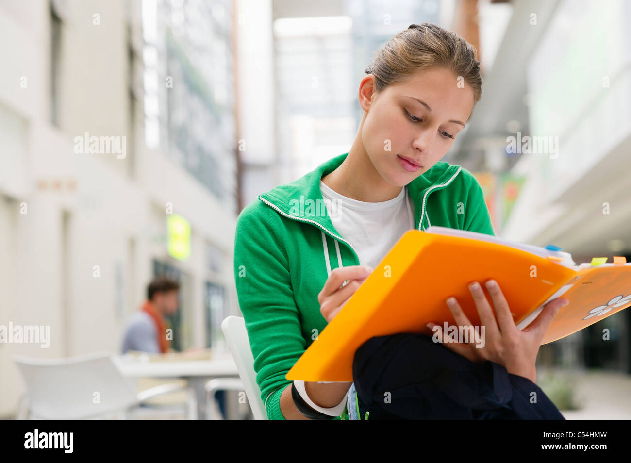 Beautiful woman studying in university lobby - Stock Image