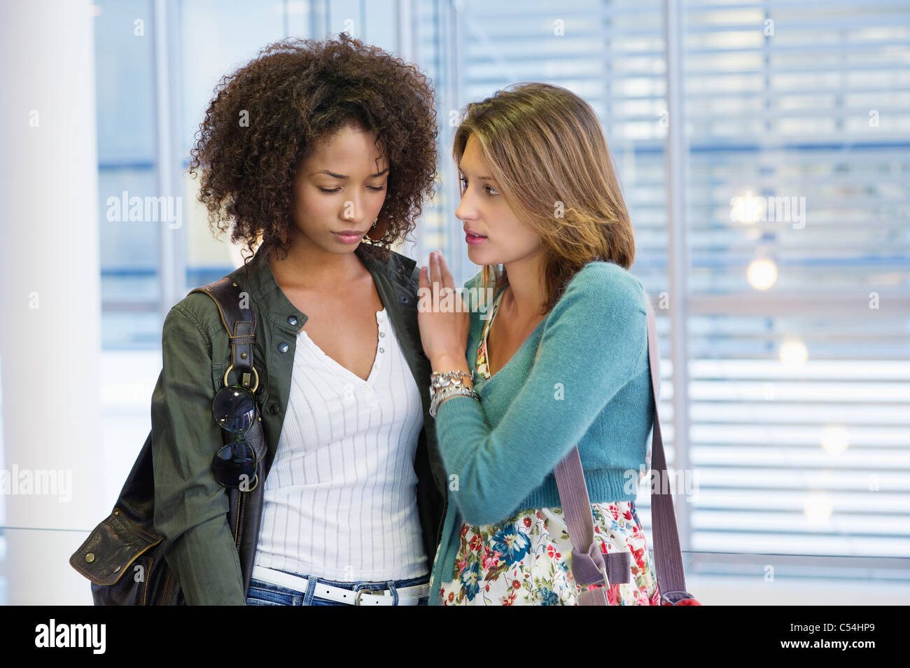Caucasian woman consoling to an African American woman in university - Stock Image