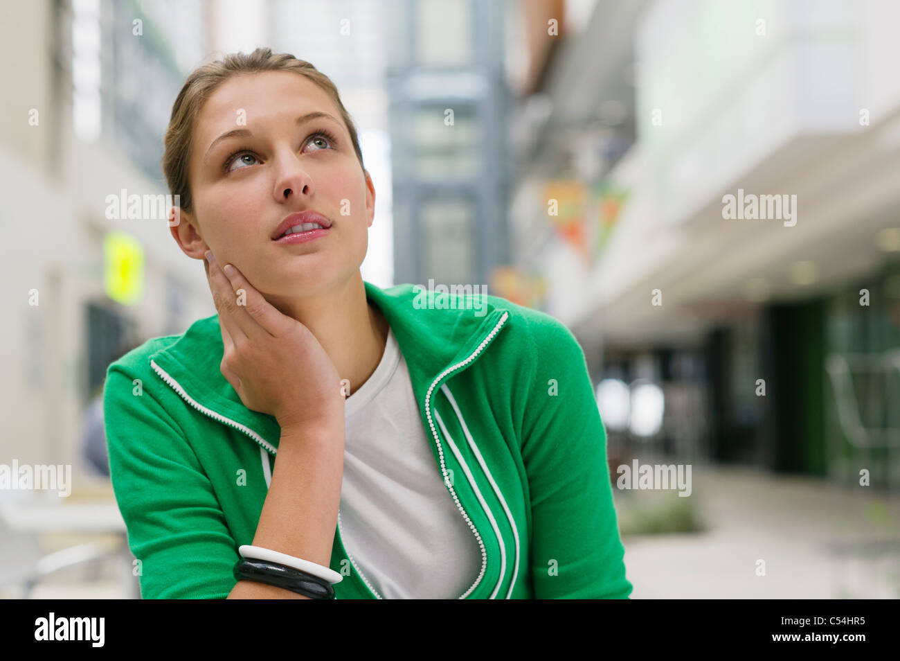 Contemplative woman looking up in a university lobby - Stock Image