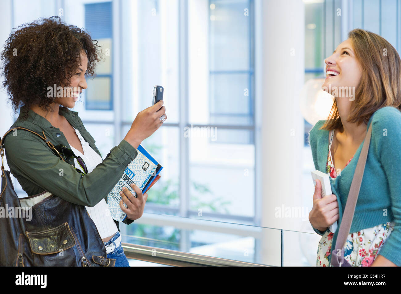 African American woman taking photos of her Caucasian friend - Stock Image
