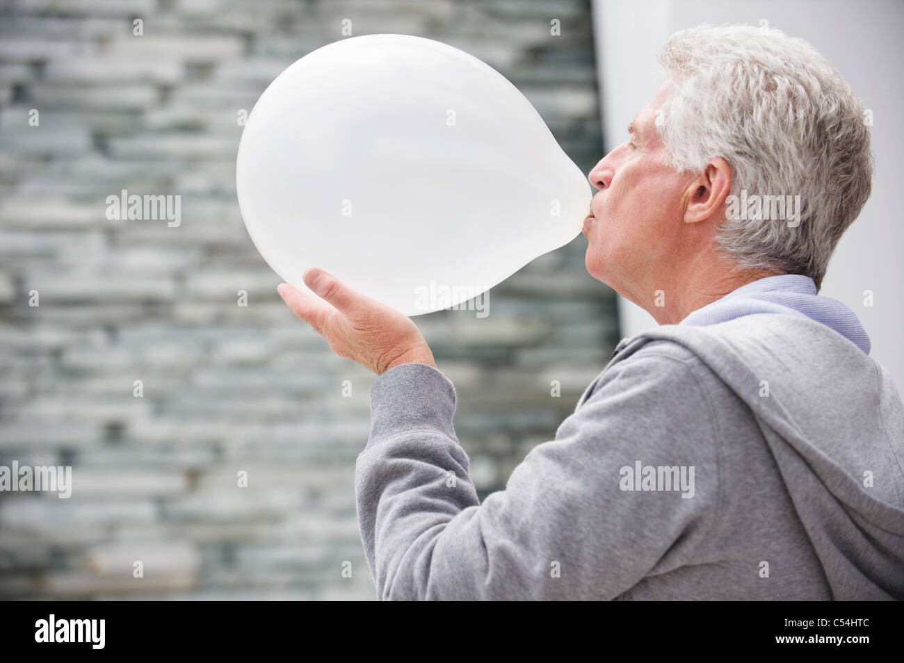 Close-up of a senior man blowing a balloon - Stock Image