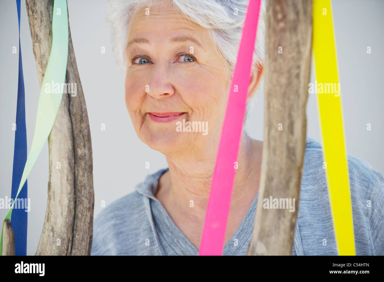 Portrait of a senior woman near a decorated tree - Stock Image