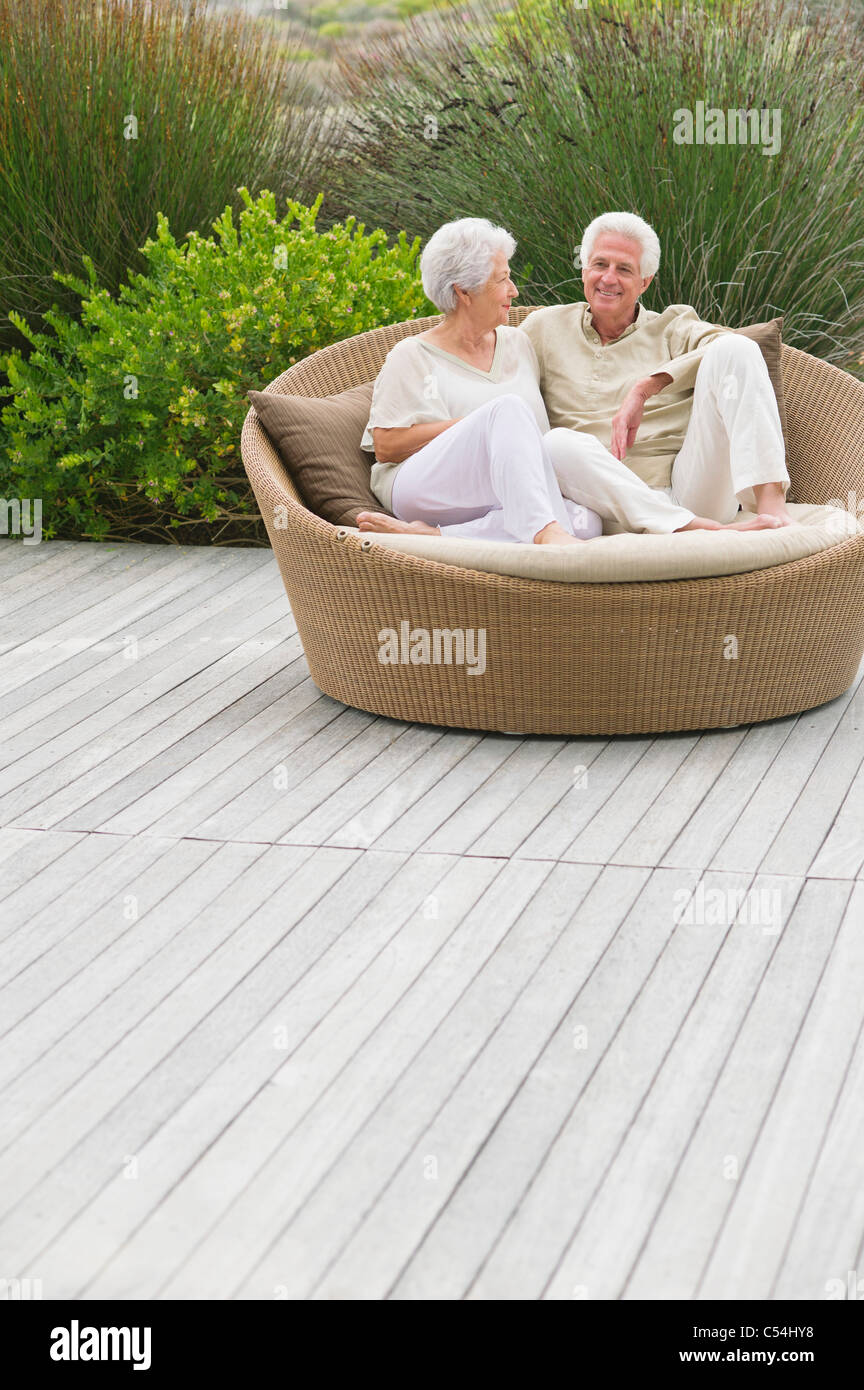 Senior couple sitting in a wicker couch - Stock Image
