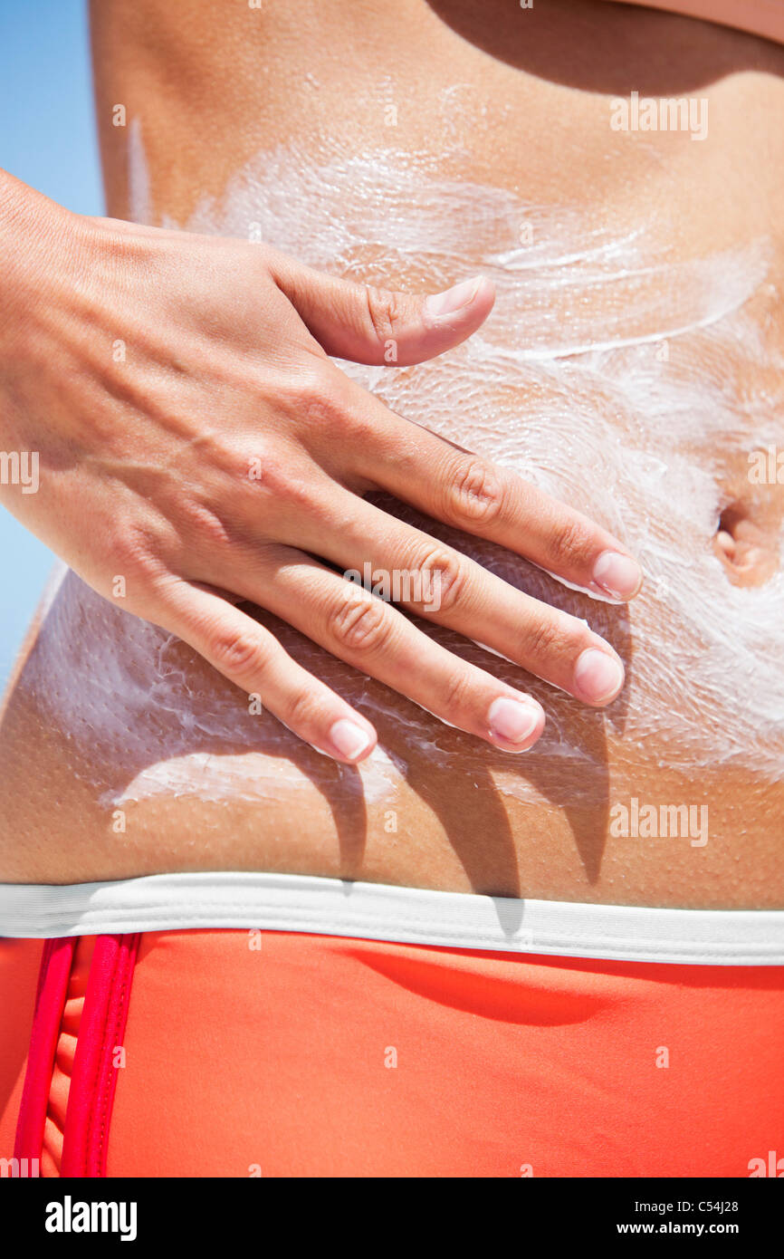 Close-up of a woman applying suntan lotion on her body - Stock Image