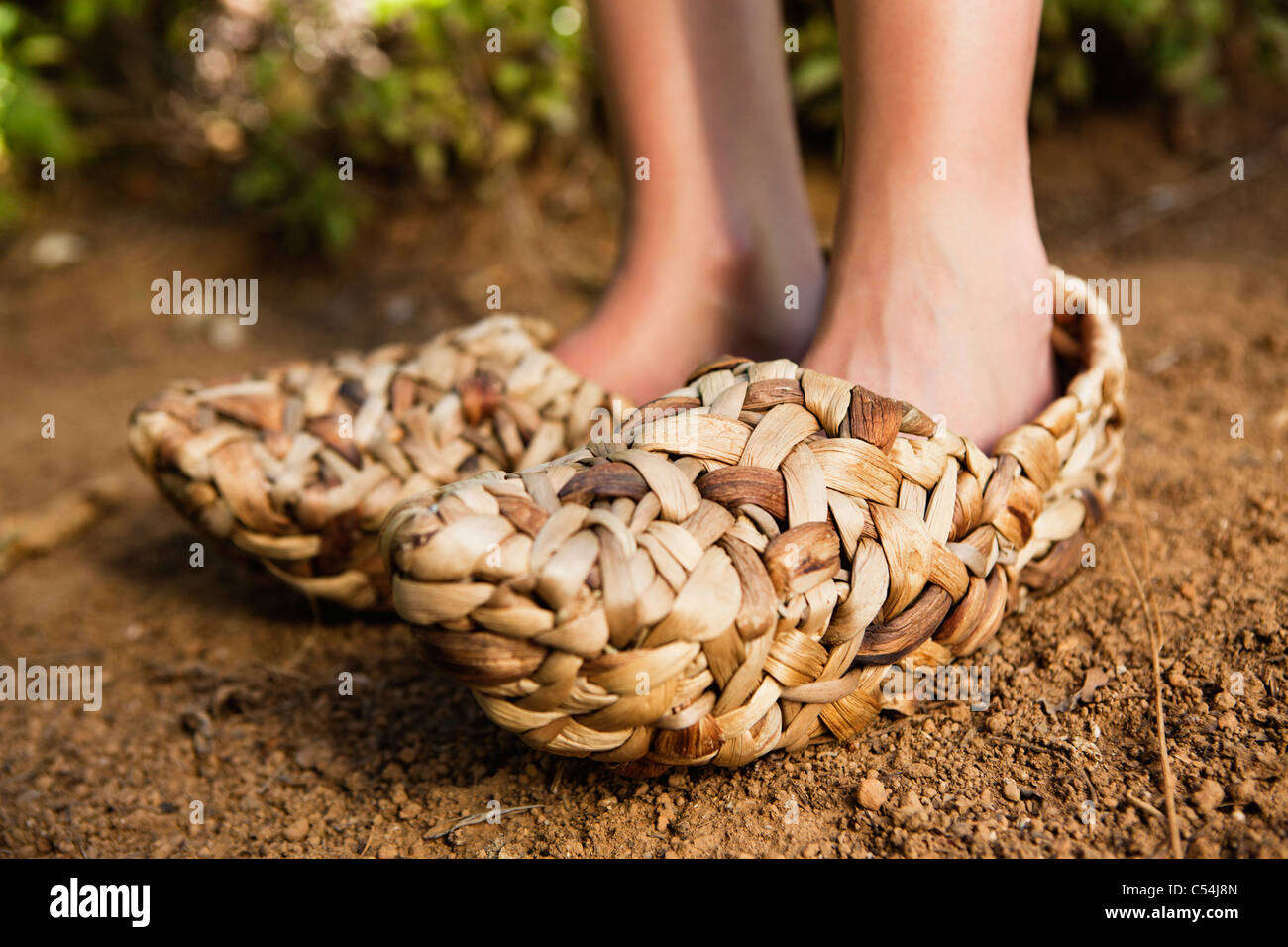 Low section view of a woman wearing wicker shoe - Stock Image