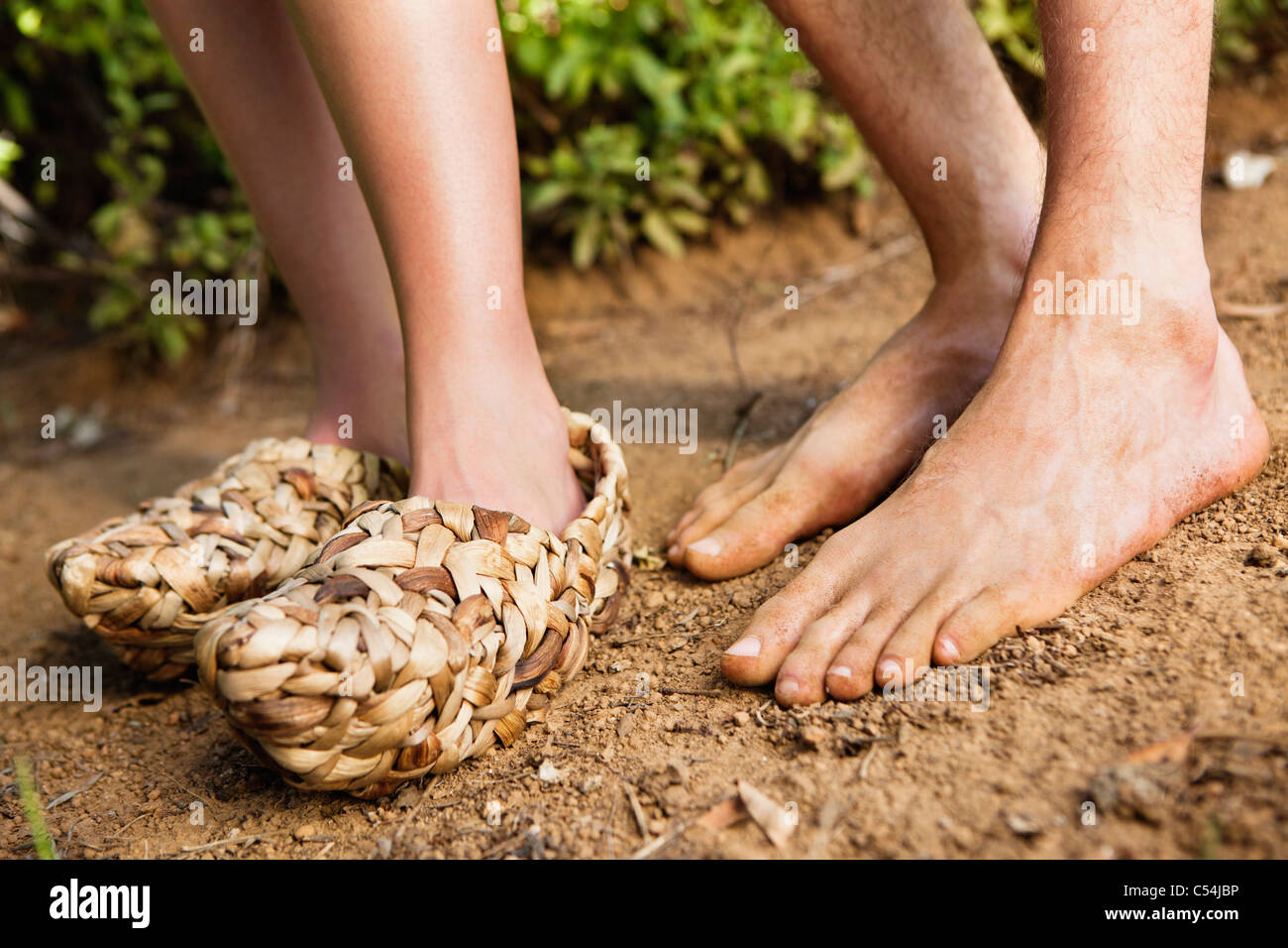 Low section view of a woman wearing wicker shoe with a barefooted man - Stock Image