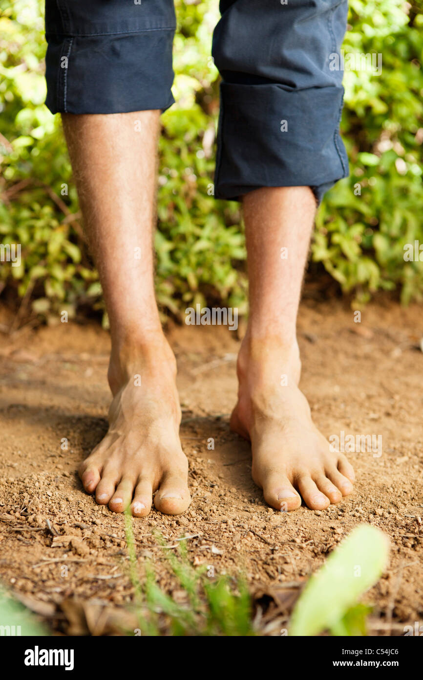 Low section view of a barefooted man - Stock Image