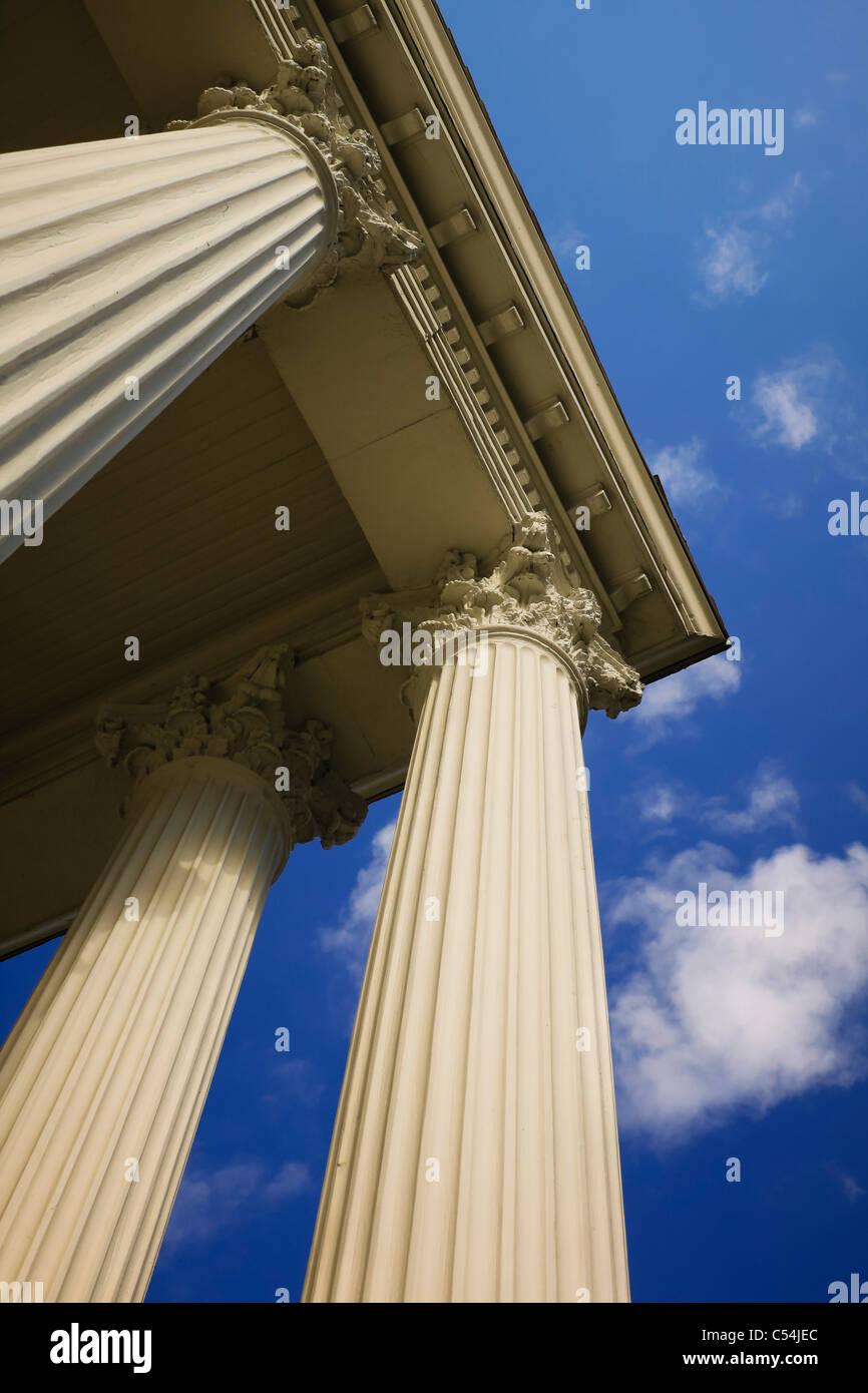 Three Corinthian columns in perspective against blue sky. - Stock Image