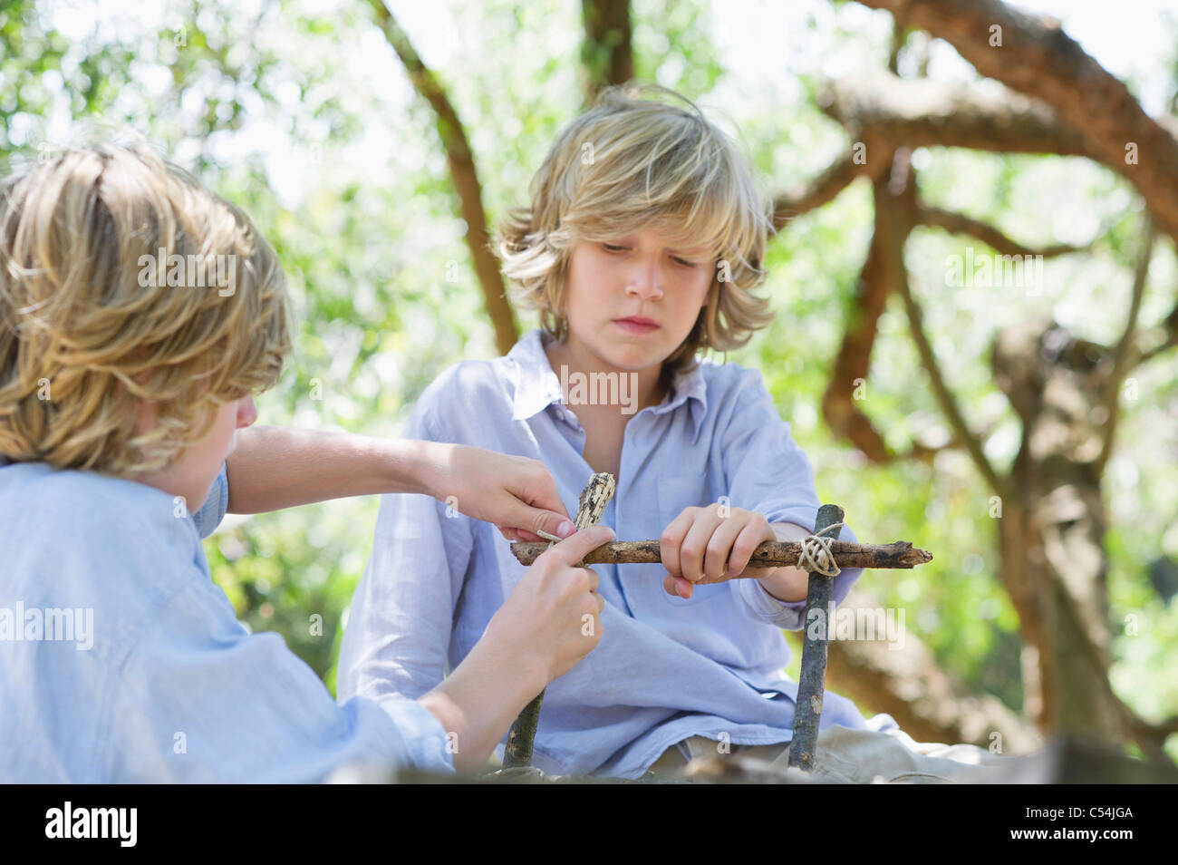Children making frame of driftwood outdoors - Stock Image