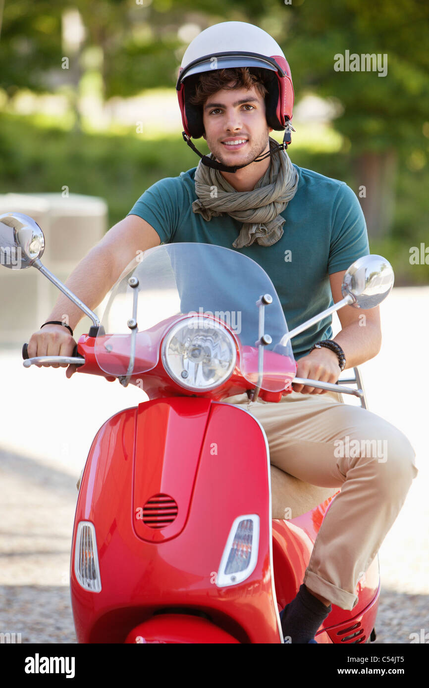 Portrait of a man riding a scooter - Stock Image