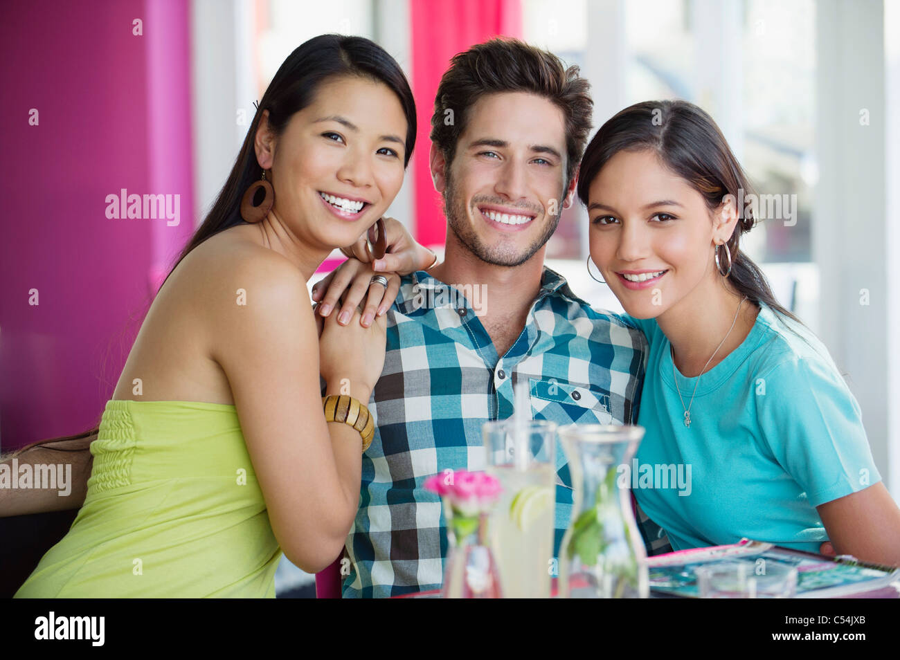 Women sitting with hand on a man's shoulders in restaurant - Stock Image