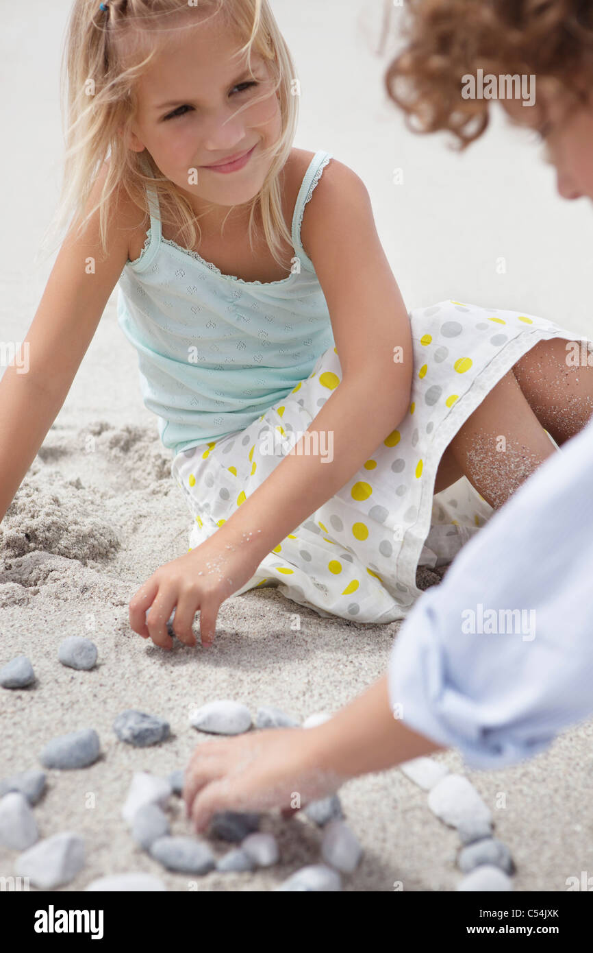 Siblings playing with pebbles on beach - Stock Image