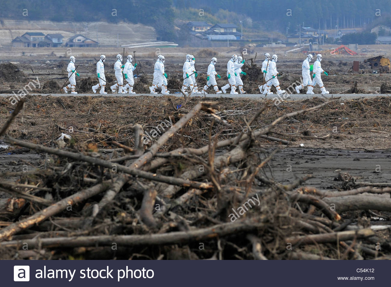 People wear protective gear, a police search party shift through debris as they search for missing people. - Stock Image