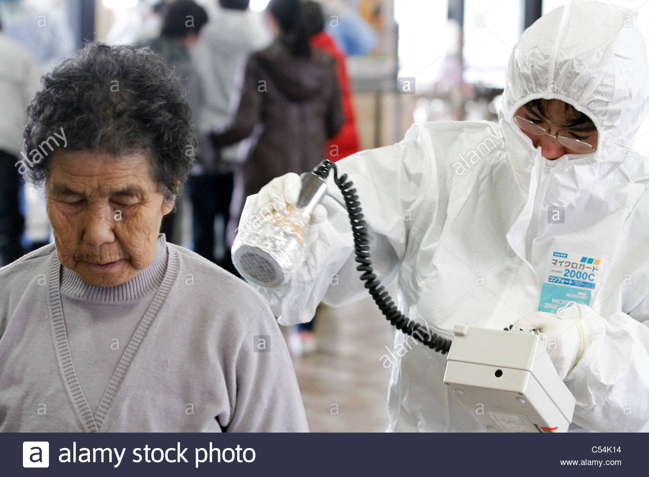 Medical staff in protective gear check radiation levels on local residents in Koriyama, Fukushima prefecture, on - Stock Image
