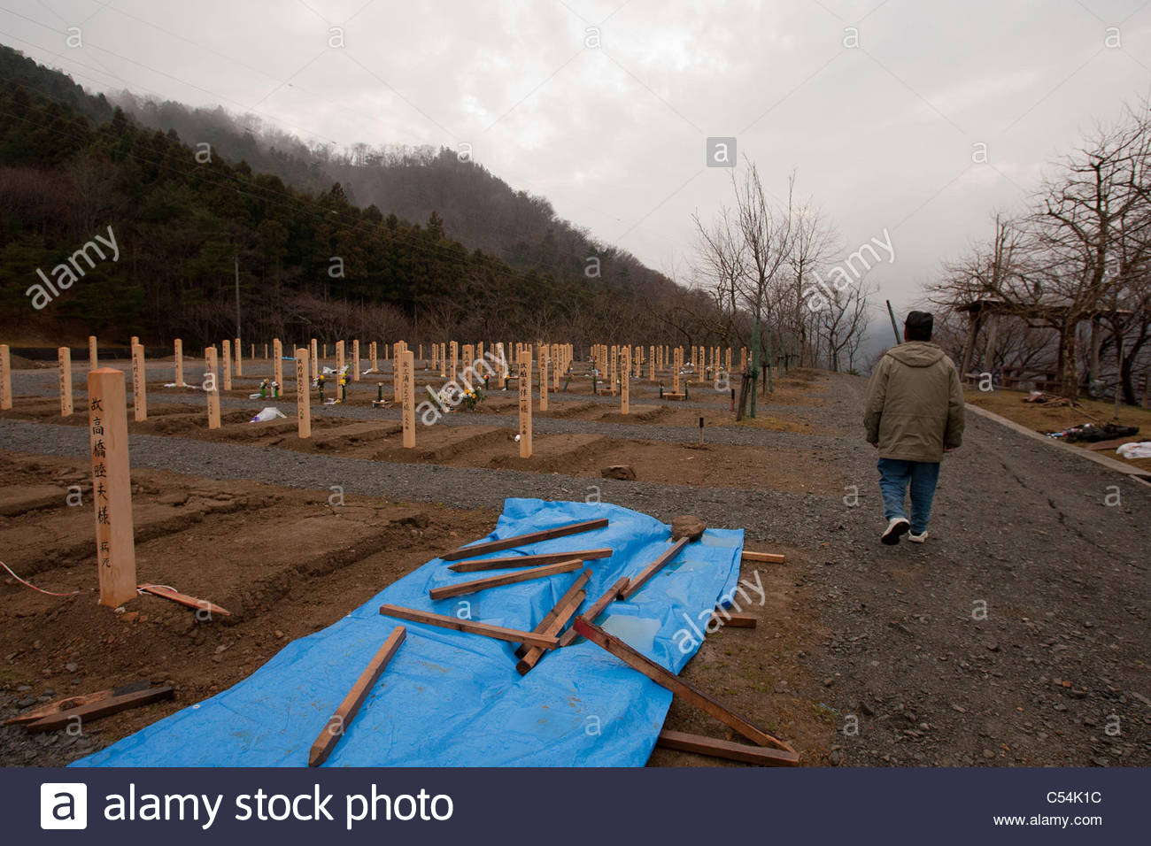 Yoshikatsu Hiratsuka, 66, walk to where his wife and mother rest in peace at a temporary mass grave for victims - Stock Image
