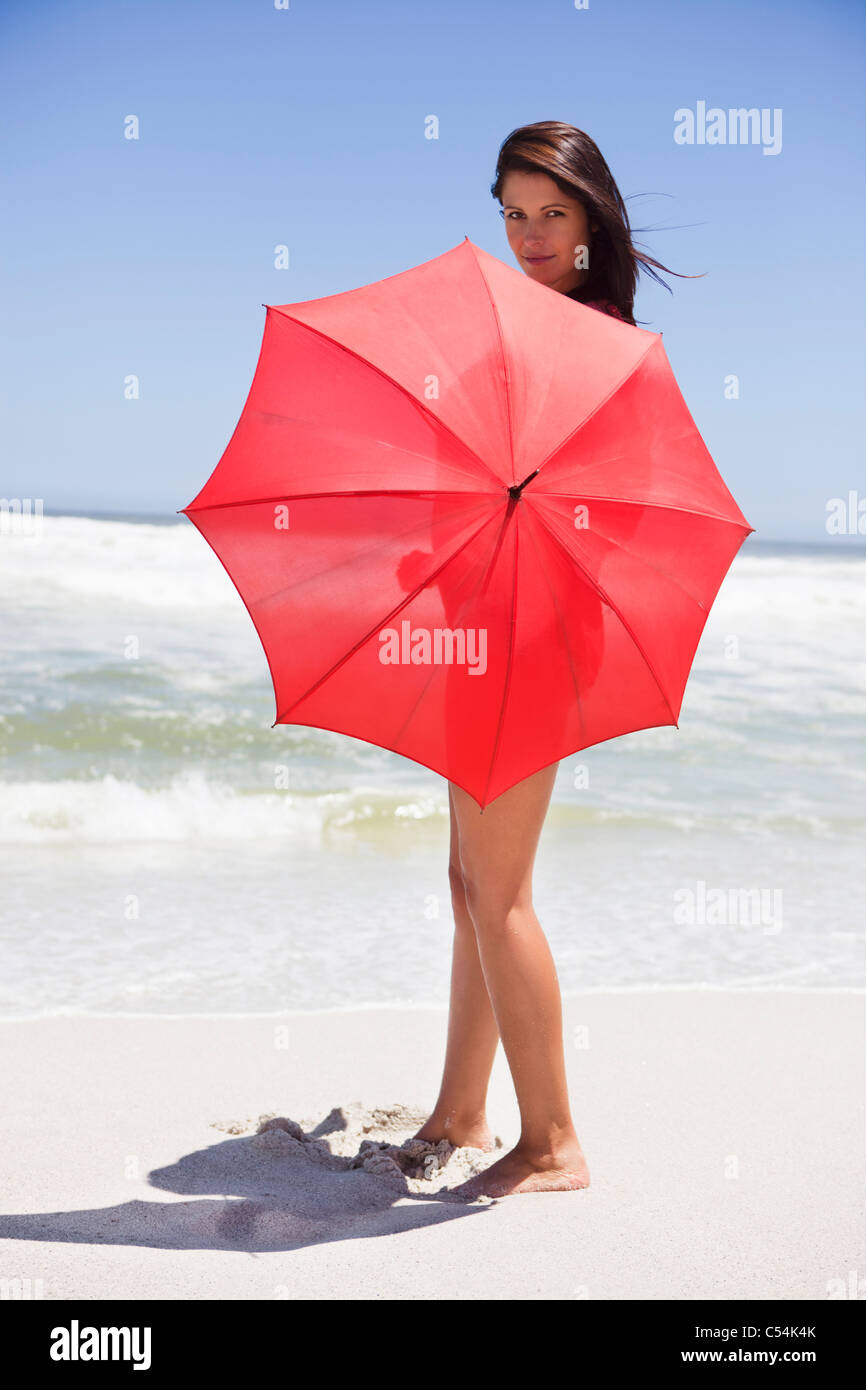 Portrait of a woman holding an umbrella on the beach - Stock Image