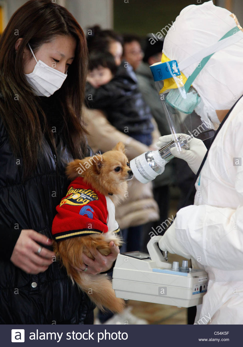 Medical staff in protective gear check radiation levels on local residents in Koriyama, Fukushima prefecture. - Stock Image