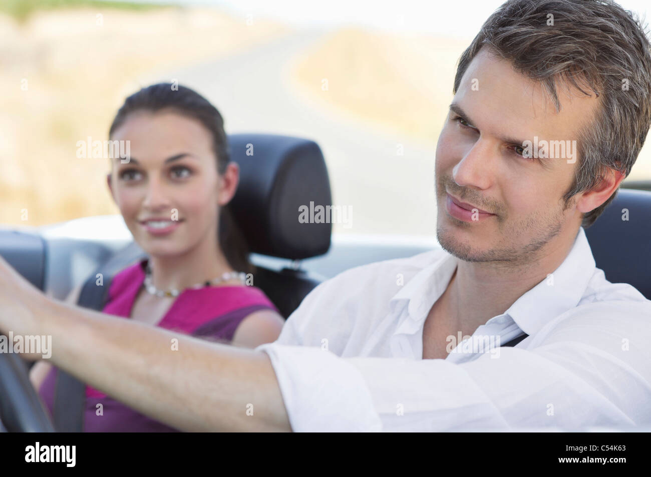 Couple driving a convertible car - Stock Image