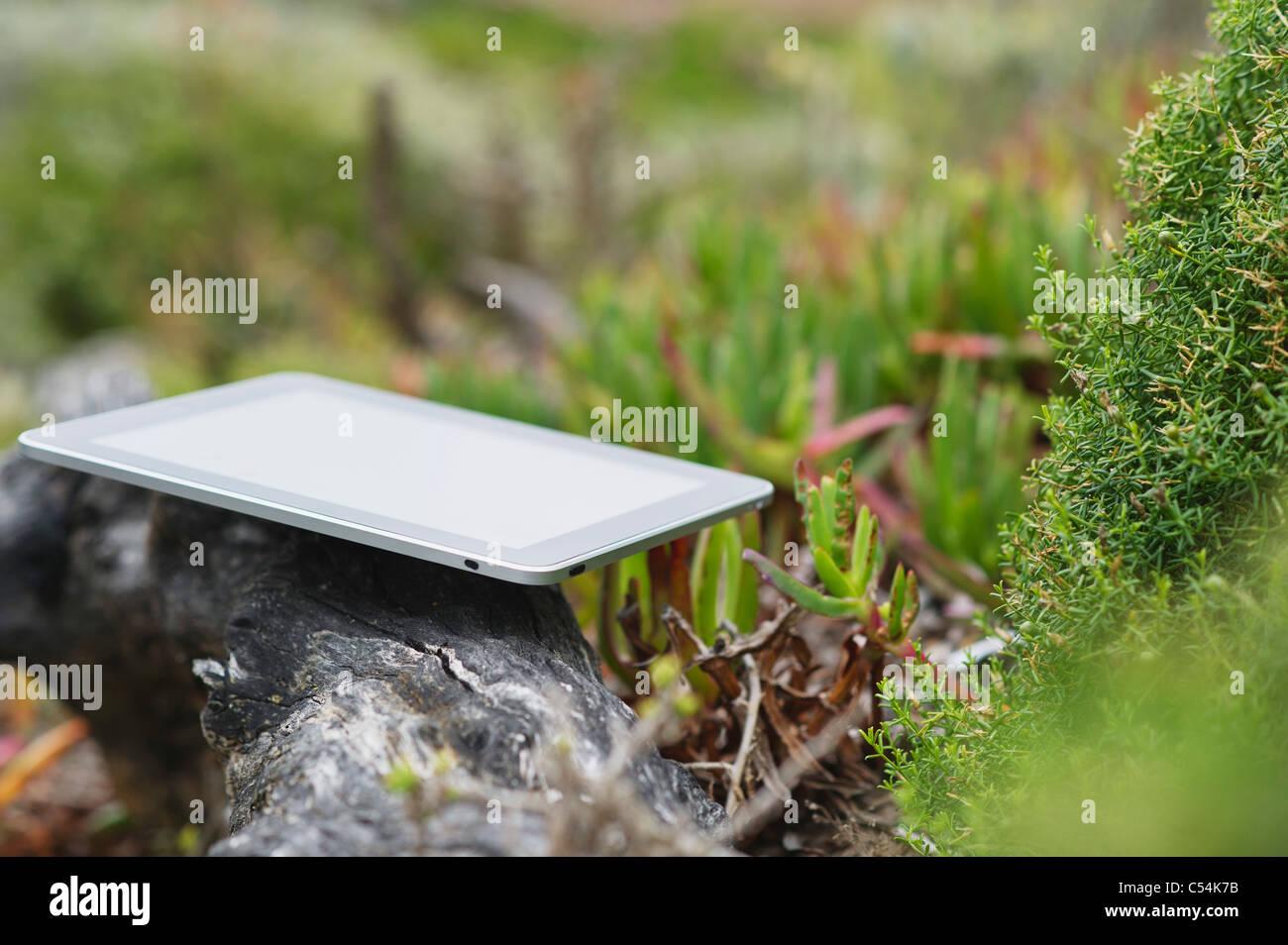Digital tablet on rock - Stock Image