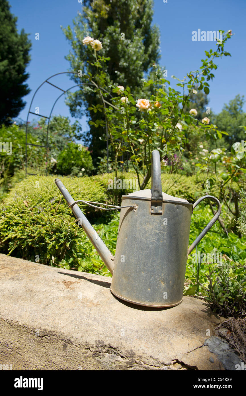 Watering can on a rock in a garden - Stock Image