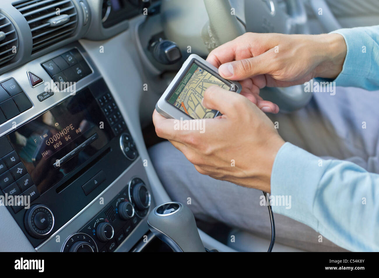 Close-up of human hand using GPS navigation system in car - Stock Image