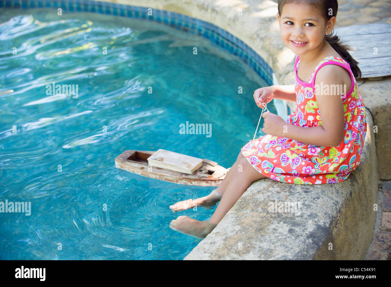 Girl sitting at edge of swimming pool with toy boat in water - Stock Image