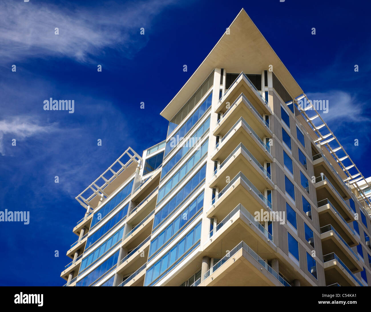 A high-end residential building with glass balconies shoot against a deep blue sky with dramatic clouds. Stock Photo