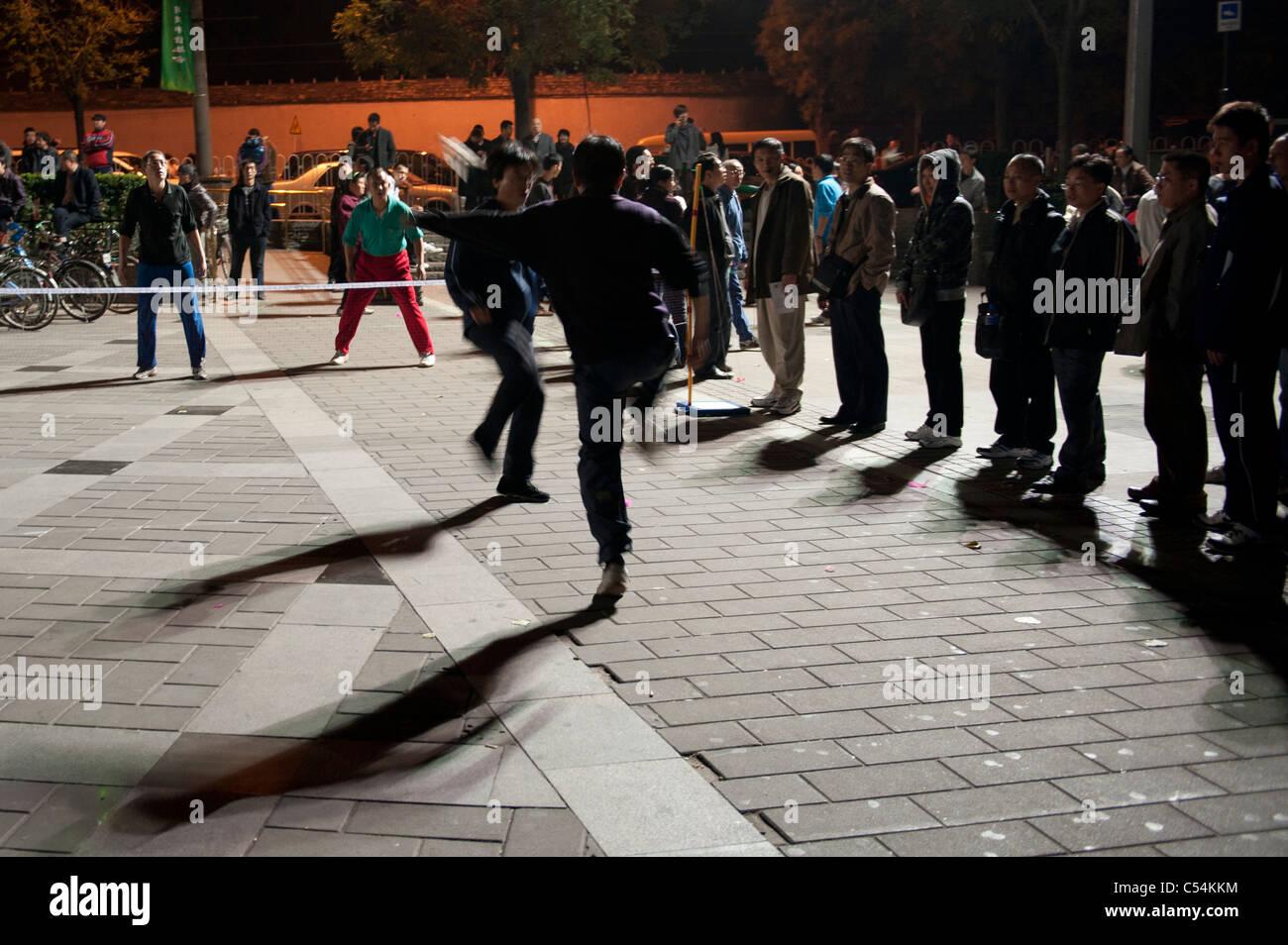 People playing feather kicker hacky sack, Back Lakes, Beijing, China - Stock Image