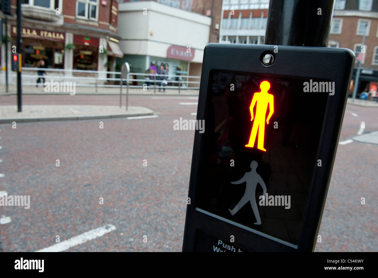 Red man symbol at a pedestrian crossing indicating it is not safe to cross the road. - Stock Image