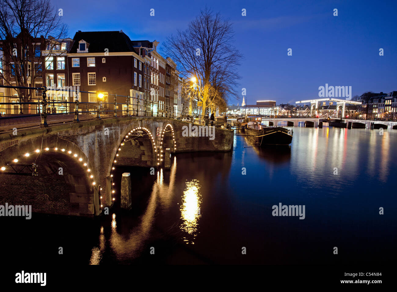 The Netherlands, Amsterdam,  17th century houses at river called Amstel. Background Skinny Bridge. Dusk. - Stock Image