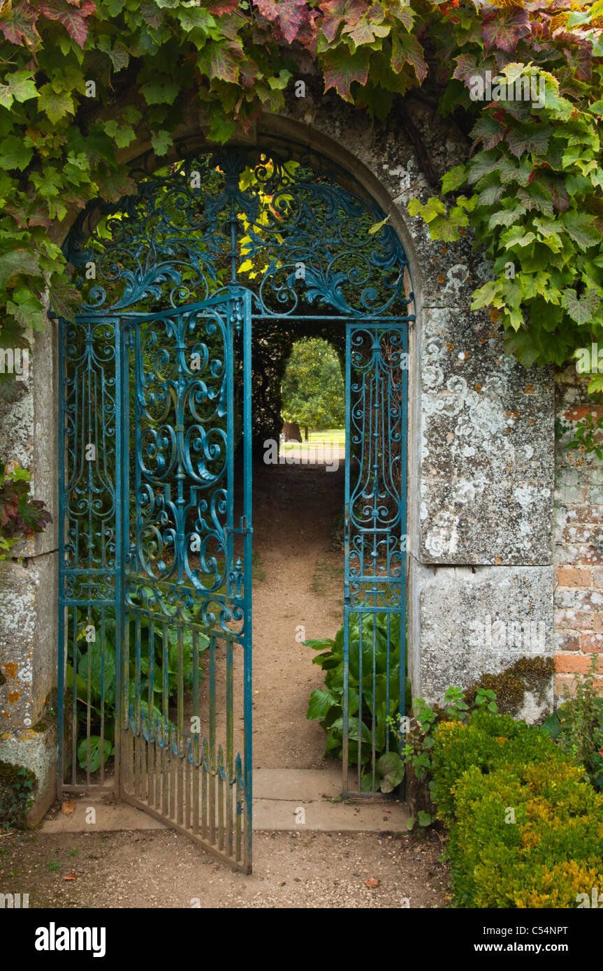 Ornate wrought iron gate set in cotswold stone arch framed