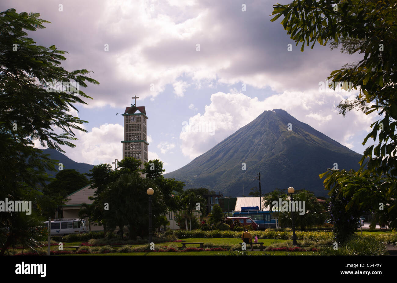 View towards Arenal Volcano from La Fortuna city square and park with church - Stock Image