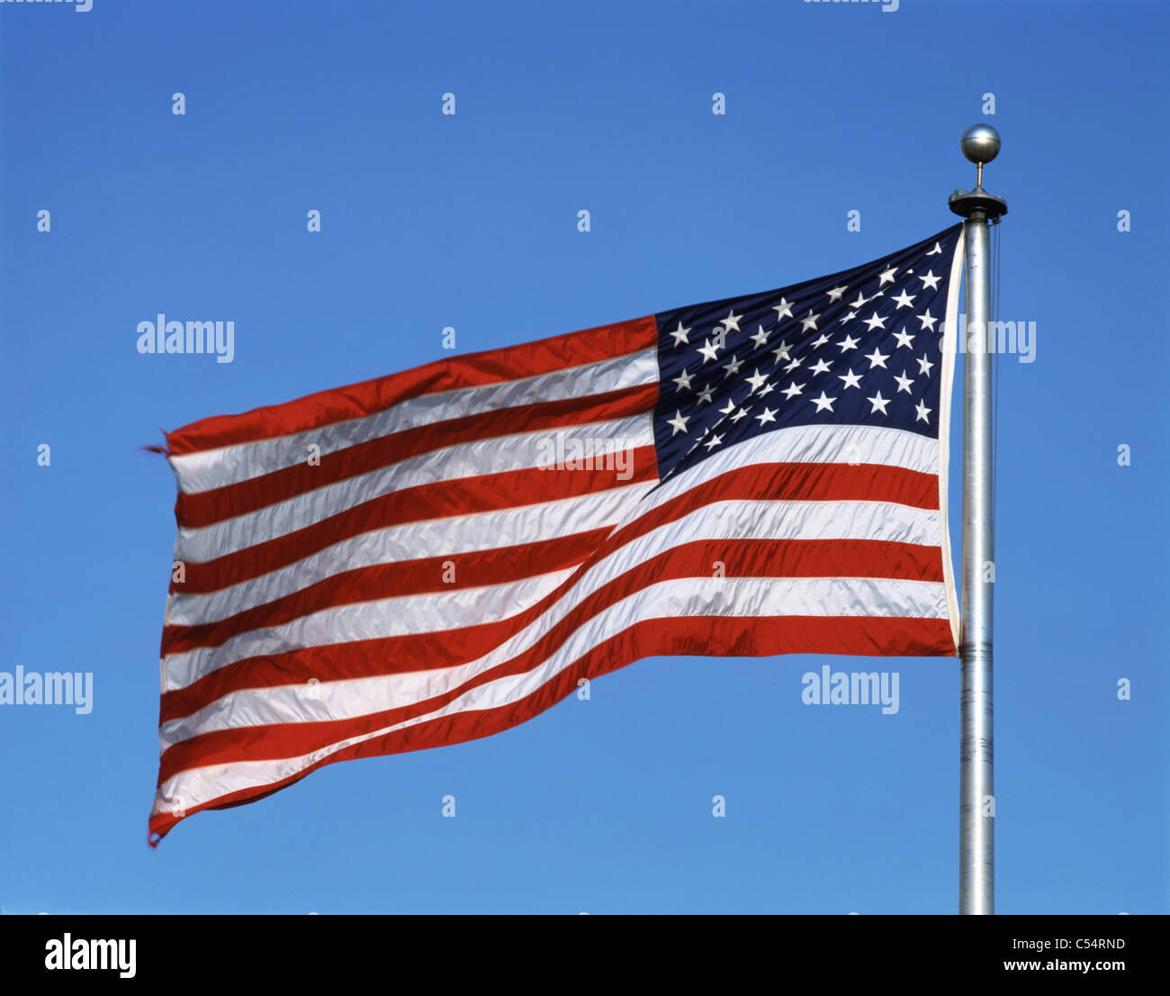 Close-up of American flag fluttering against blue sky Stock Photo
