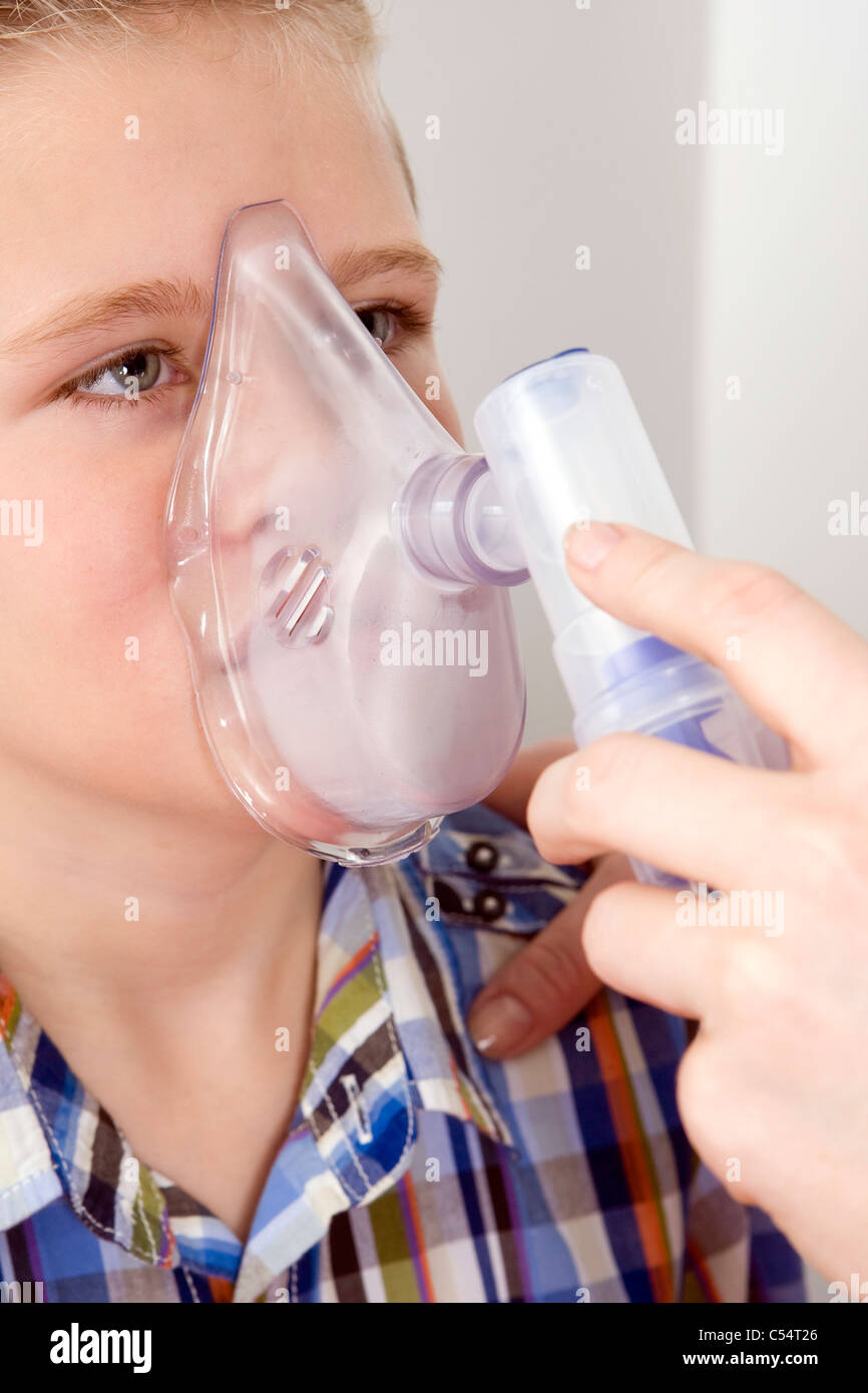 A Nurse tests the lung capacity of a ten year-old boy using a digital peak flow meter. - Stock Image