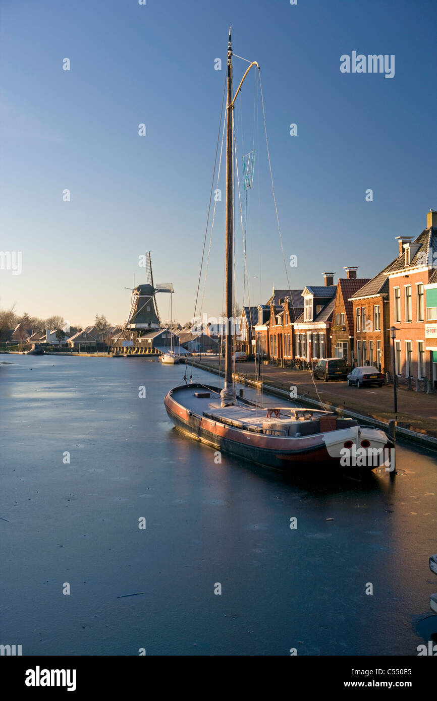 The Netherlands, Woudsend, Traditional cargo ship, now sailing boat for tourism in frozen canal. Background windmill. - Stock Image