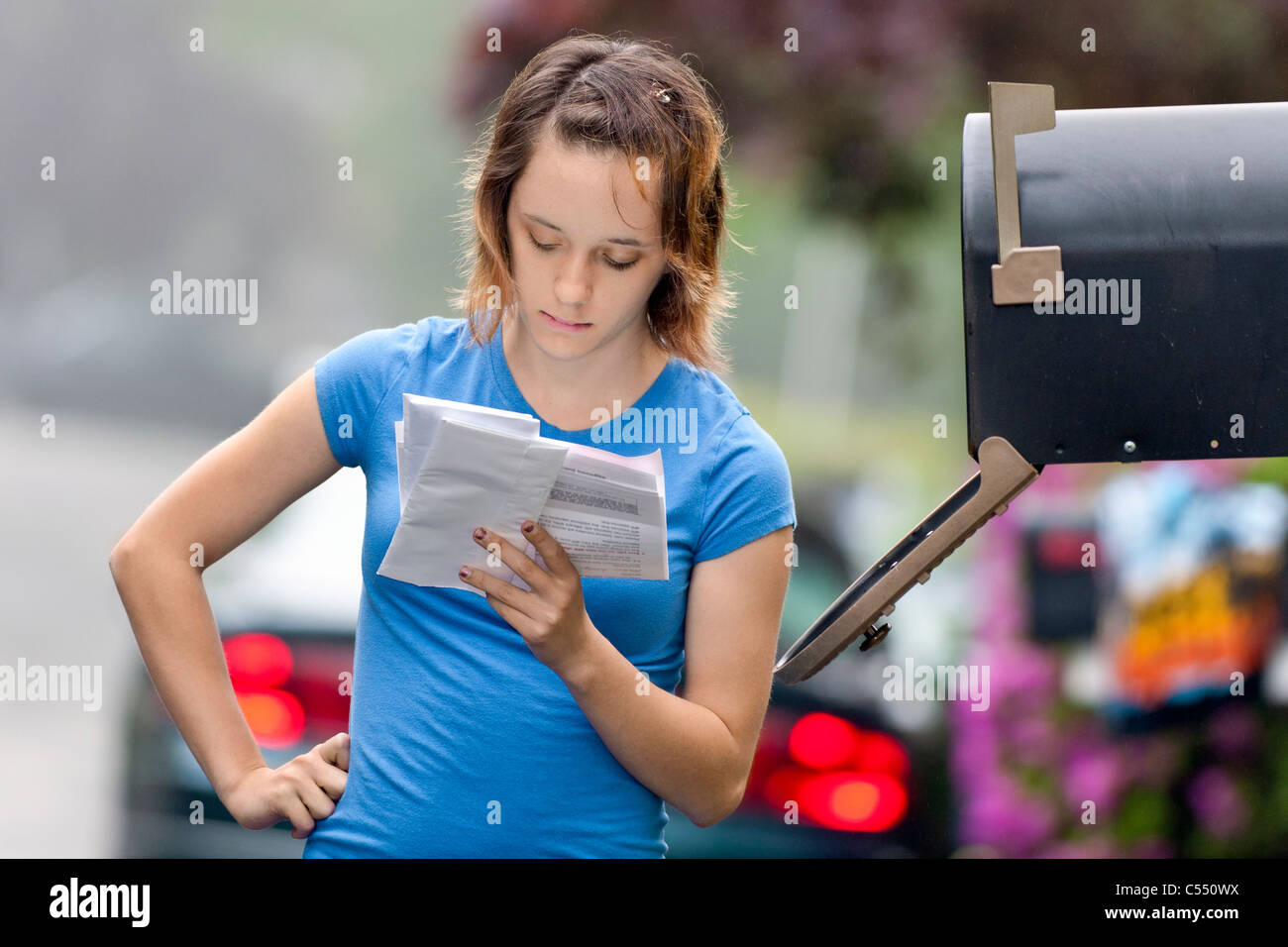 Teenage Girl reading the mail by the mailbox. - Stock Image