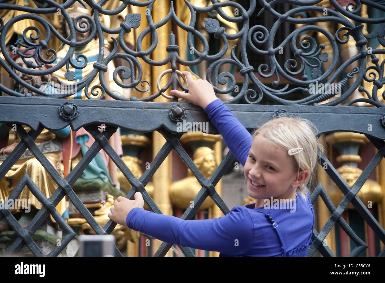 Kind dreht den Ring am Schoenen Brunnen Hauptmarkt Little girl rotate the ring at the beautiful well main market - Stock Image