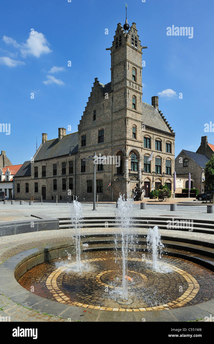 Fountain and old town hall with belfry at Lo, Lo-Reninge, Belgium - Stock Image