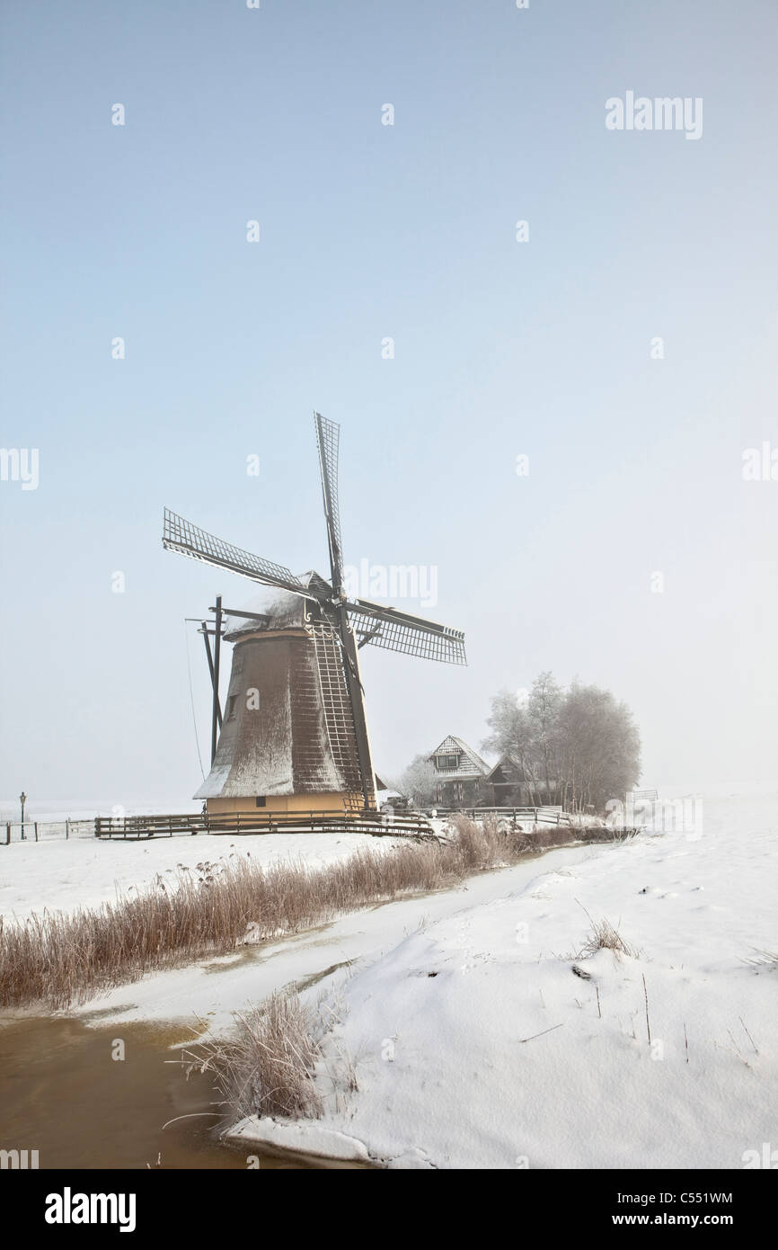 The Netherlands, Workum, Windmill in snow landscape. - Stock Image