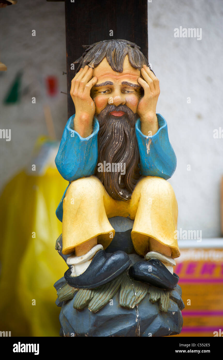 Funny wood carving of a sad and troubled old man in Schwarzwald, Germany - Stock Image