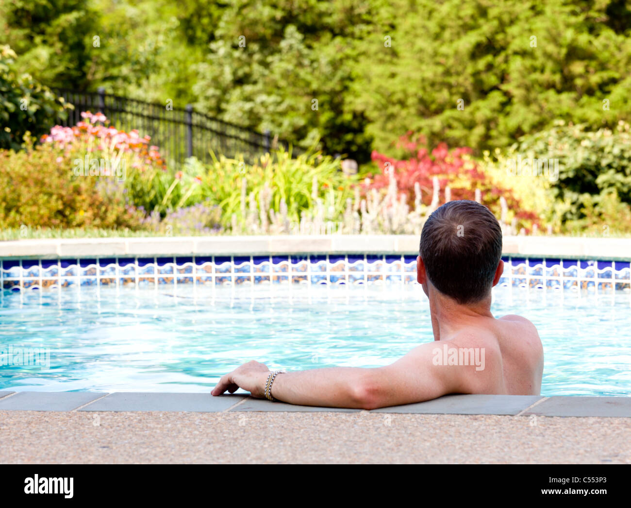 Man Relaxing By The Side Of A Swimming Pool At Home In The Garden And Stock Photo Alamy