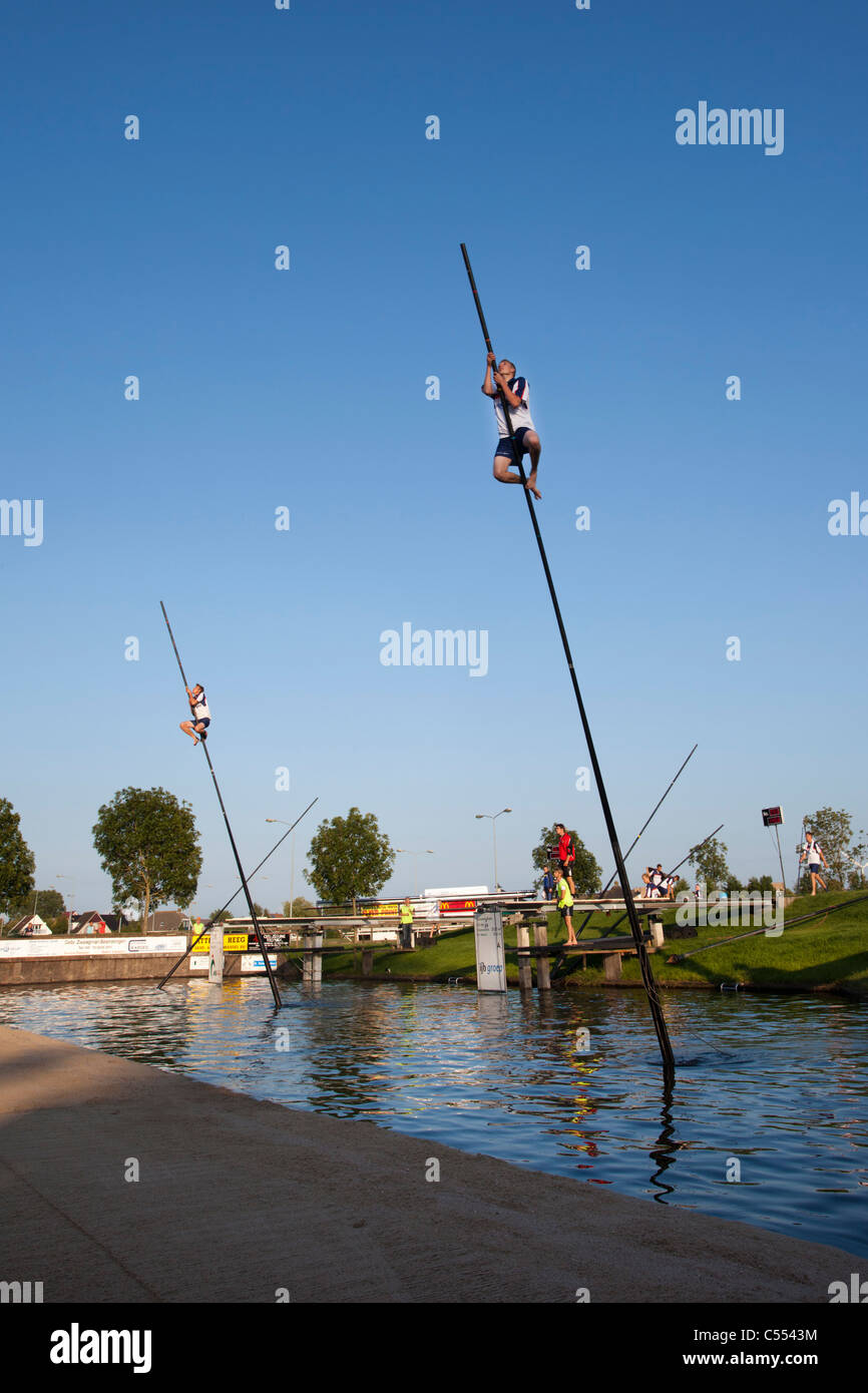 The Netherlands, IJlst, Competition of fenpoling, locally called Fierljeppen, crossing the water as far as you can. - Stock Image