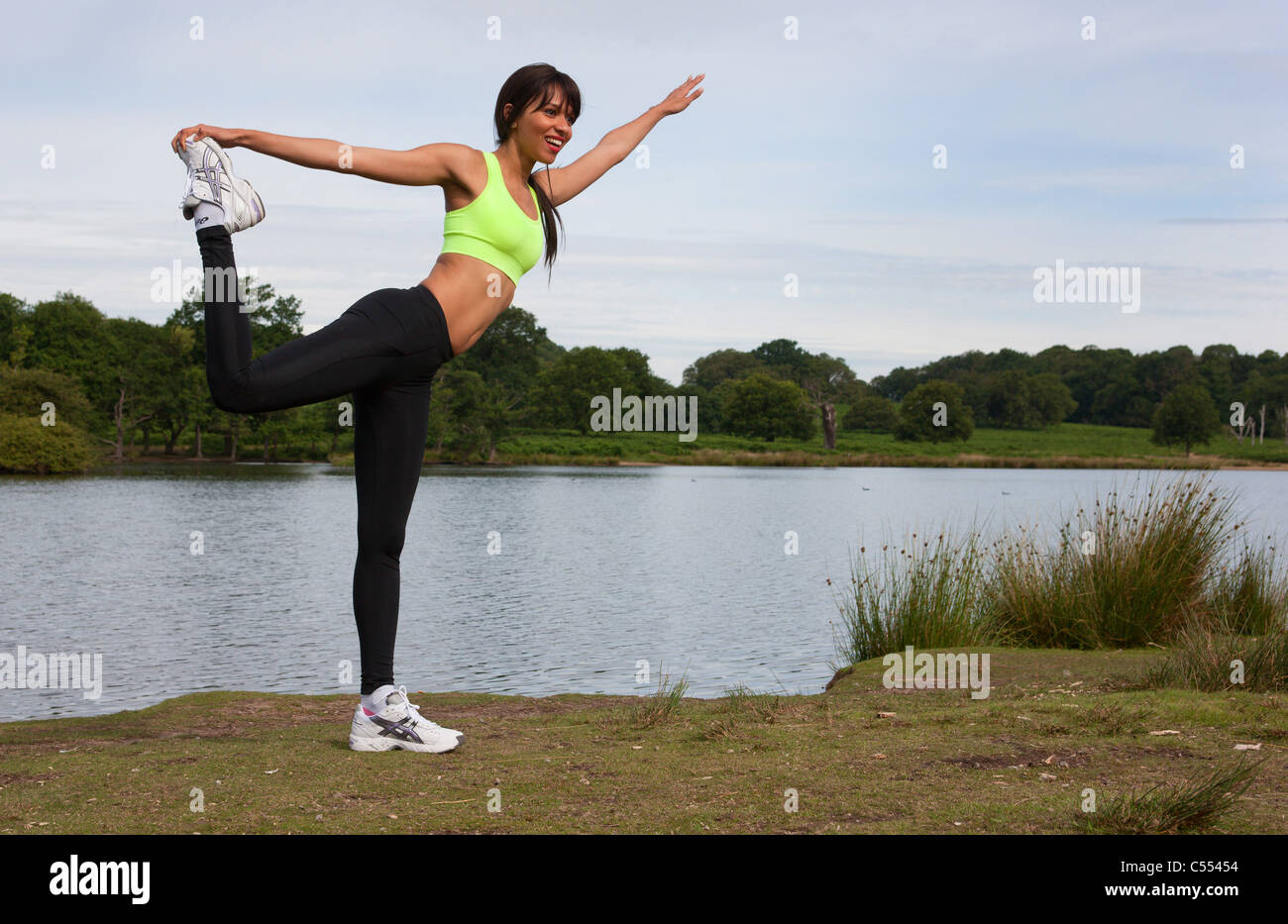 a young woman warms up for her fitness workout next to a lake stock