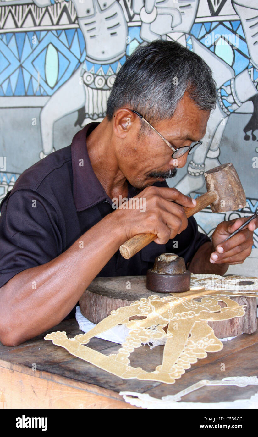 A Javanese Man Creating a Wayang Kulit or Traditional Shadow Puppet. - Stock Image